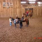  Kids getting horsemanship lesson in the indoor arena