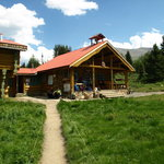 Mt. Assiniboine Lodge.  Living room with lodge rooms upstaisr on left.  Dining room and kitchen