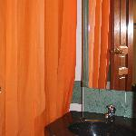 Bright orange shower curtain - shower over bathtub.