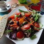 Lightly dressed mixed green salad with delicious olives and hearty bread