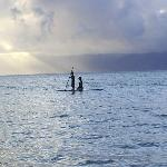 My wife and son paddle boarding in front of the Hololani Resort