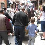 Riad porter holding our son's hand tightly, whilst transporting our baggage through the medina!