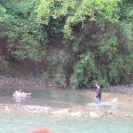 Vacationers (mostly Japanese) build stone pools around hot springs in the river bank