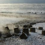 Steaming hot spring on snow covered beach