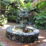 Courtyard features a fountain and an abundance of plants.