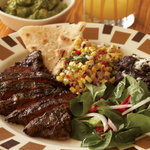Grilled skirt steak with charred corn relish, black beans, tomato avocado salad, and handmade fl