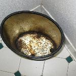  Rusted trash can in bathroom.