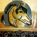 Beautiful Horse face carved into the wood of the booth/table.