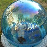 This is the reviewer inside the gazing ball along with a view of mansion and palm trees.