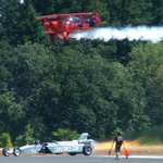 Jet car drag racing against biplane