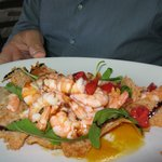 Giant prawns on a bed of arugula, tomatoes, a top a fried parmesan tortilla... amazing!! And onl