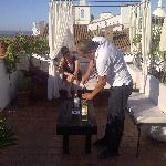 Joao serving wine on the terrace while the sun sets