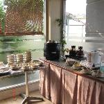 A corner of the breakfast buffet station with porridge, coffee and tea, toast and assortment of