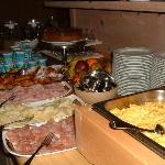 Scrambled eggs, boilled eggs, salami, cheese, fruit, croassain, juicet...