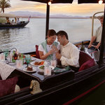 A couple enjoys a romantic dinner aboard a gondola on Lake Las Vegas