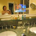 A TV in the bathroom mirror!