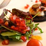 Tender scallops gently grilled, presented with juice pomegranate seeds and a thin slice of black