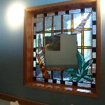 Mosaic mirror on partial wall separating ensuite from main bedroom
