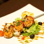 Grilled tiger prawns with roasted pepper sauce and potato gratin.