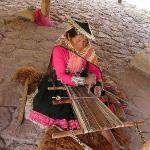  At a weaving coop, a woman plies her ancient craft