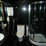 bathroom full of black marble and glass