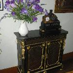 a wonderful cabinet with a beautiful clock complemented by fresh irises
