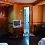 The closet, tv aand mini bar with door to the bathroom