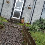 view of front door with dead plants. quite unweldoming