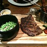  Rib-eye steak with sweet potato chips and french peas, bacon and baby onions.
