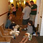  5 familys sharing pizza in the 3rd floor hallway.