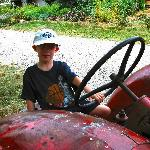 A boy driving an ancient tractor.