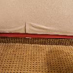 Red tape holding up the wallpaper and stains on carpet.