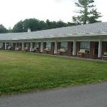  Front view of motel with chairs outside units.