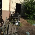 "To the right of the rear ""middle"" entry door: junk, BBQs & a bench"
