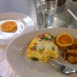 A gluten free omelet with an extra lonely orange slice as a substitution for the pastry and brea