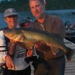 Cindy and her 33 inch walleye with help from Dave