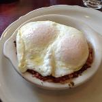 corn beef hash with over easy eggs served with a side of 3 pancakes.