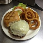 Brewster burger topped with swiss cheese and served with onion rings