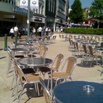 "The square taken over by empty tables & chairs of a ""coffee bar"""