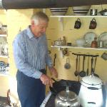  Denley demonstrating cooking with a wood-fired stove.