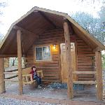 Front of cabin with hanging swing under the porch.