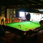 Playing snooker. Old fussball game just to the right. Billiards to the left.