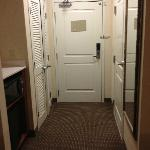 Entry hall with large closet with plenty of hangers, microwave and refrigerator.