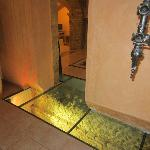 Glass floor tiles reveal the historic stone foundations