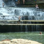 falls. you can jump off into pool where the child that is front center is standing.