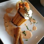 Poached egg atop stuffed squash with roasted potatoes and carrots in a parmesan cheese basket