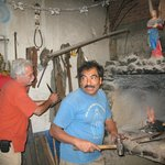  Alvin (left) works the bellows to fire up the knife maker&#39;s oven