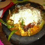 Molcajete! Shrimp, chicken, & beef fajitas brought to the table in a bubbling Calderon topped wi