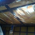  leak stained ceiling with plastic sheeting to keep the water out