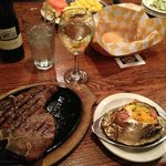 A delicious porterhouse steak with a loaded baked potato